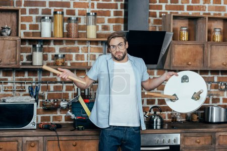 disappointed young man in eyeglasses holding broken stool and looking at camera