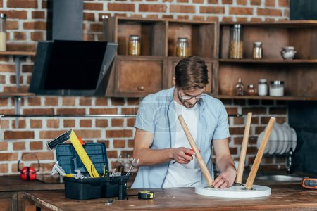 focused young man in eyeglasses holding screwdriver and repairing stool with screwdriver