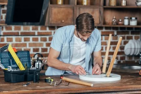 Photo pour Jeune homme occasionnel réparer tabouret avec des outils à la maison - image libre de droit