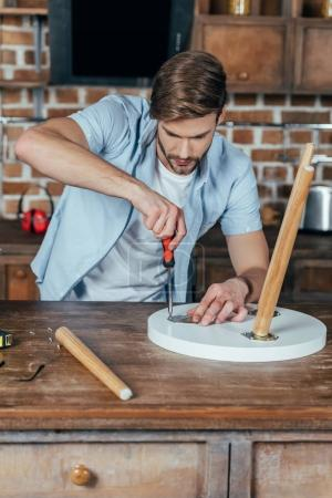 handsome young man repairing stool with screwdriver