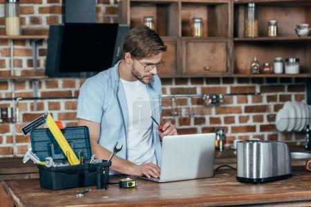 young man in eyeglasses using laptop while repairing toaster at home