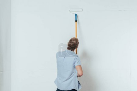 back view of young man using paint roller while painting wall at home