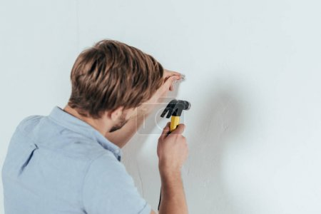 back view of young man hammering nail in wall at home