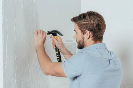 young man hammering nail in wall at home