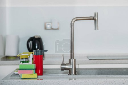 dishwashing sponges near water tap in kitchen