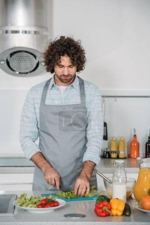 handsome man cutting vegetables for salad