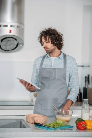 handsome man searching for recipe and looking at tablet