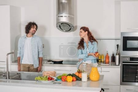 happy couple standing at kitchen and looking at each other