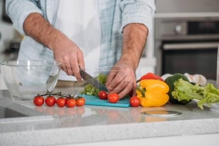 cropped image of man cutting vegetables for salad