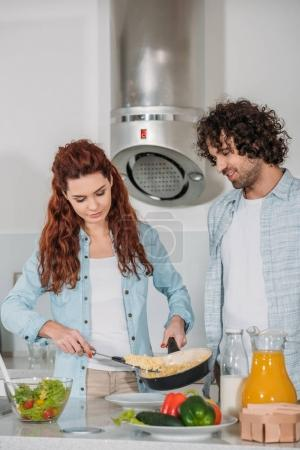 Photo for Girlfriend putting omelet on plate and boyfriend looking at food - Royalty Free Image