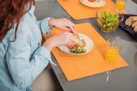 cropped image of woman eating at table in kitchen