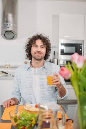 smiling man sitting at table with meal and holding glass of orange juice
