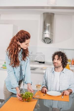 Photo for Smiling girlfriend putting salad on table and looking at boyfriend - Royalty Free Image