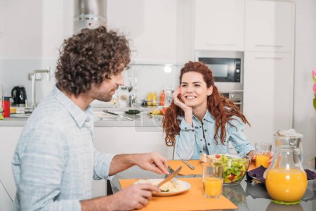 Photo for Smiling girlfriend looking how boyfriend eating homemade food - Royalty Free Image