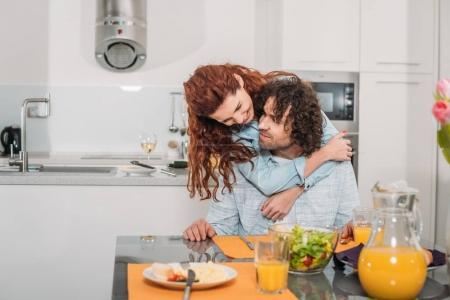 Photo for Happy girlfriend hugging boyfriend from back at kitchen - Royalty Free Image
