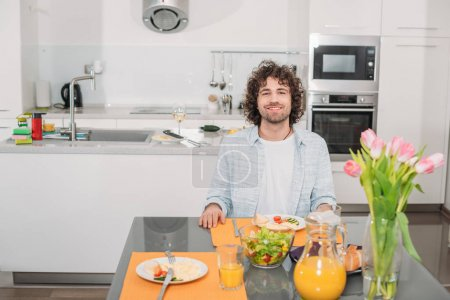 Photo for Smiling man sitting at table with food and looking at camera - Royalty Free Image