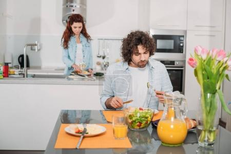 Photo for Boyfriend eating while girlfriend cooking at kitchen - Royalty Free Image
