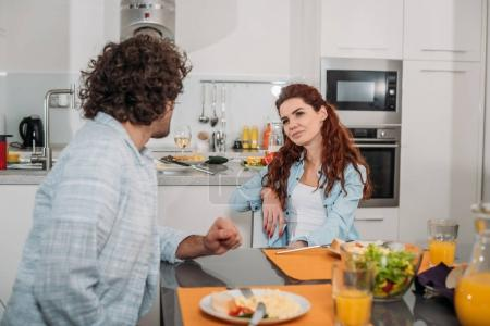 couple talking while sitting at table with food