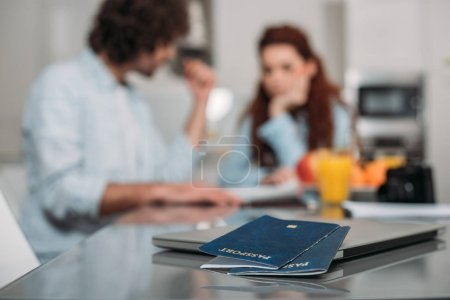 couple planning trip with passports on foreground