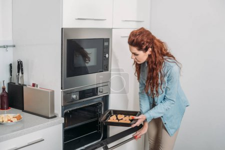 woman taking homemade biscuits from oven