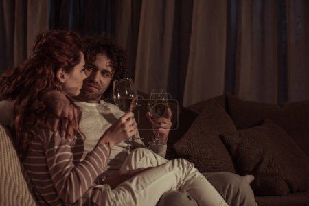 couple sitting on sofa with glasses of champagne in evening