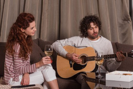 handsome boyfriend playing song with guitar for smiling girlfriend