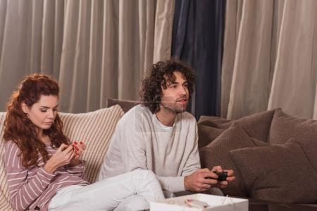 girlfriend waiting while boyfriend playing video game