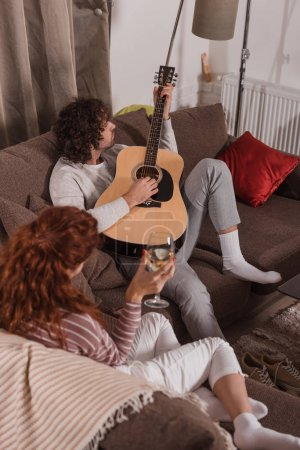 Photo for Handsome boyfriend playing song with guitar to girlfriend at home - Royalty Free Image