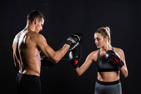 Photo for Side view of athletic young couple boxing isolated on black - Royalty Free Image