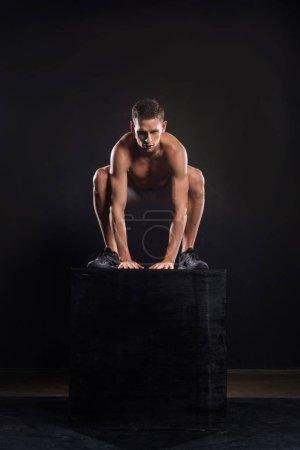 Photo pour Sportif torse nu sportif jeune sautant de bloc sur fond noir - image libre de droit
