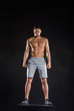 full length view of shirtless muscular sportsman standing on block and looking at camera on black