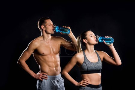 Photo for Athletic young couple in sportswear drinking from bottles isolated on black - Royalty Free Image