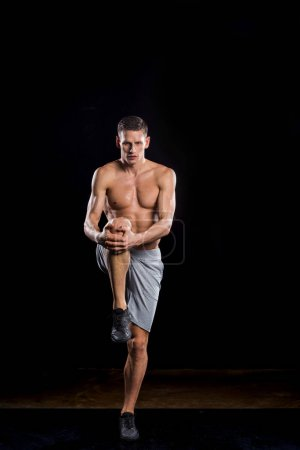 muscular young sportsman holding knee in hands and looking at camera on black