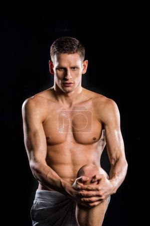 muscular young sportsman holding knee in hands and looking at camera isolated on black