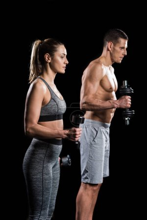 young sportsman and sportswoman exercising with dumbbells isolated on black