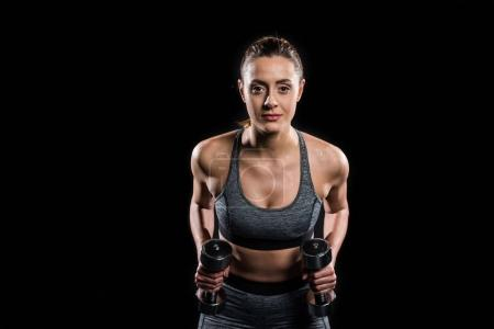 athletic young woman in sportswear exercising with dumbbells and looking at camera isolated on black