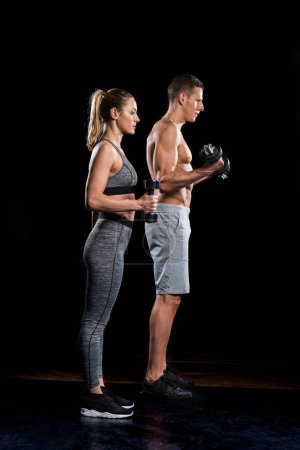 side view of sporty young couple exercising with dumbbells on black