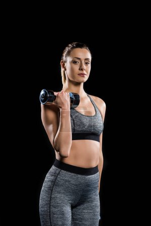 Photo for Athletic sportswoman holding dumbbell and looking at camera isolated on black - Royalty Free Image