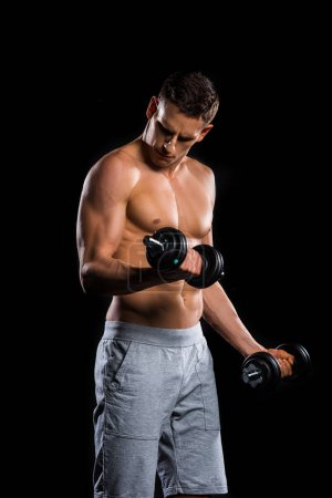 muscular shirtless sportsman training with dumbbells isolated on black