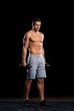 muscular shirtless sportsman holding dumbbells and looking at camera on black