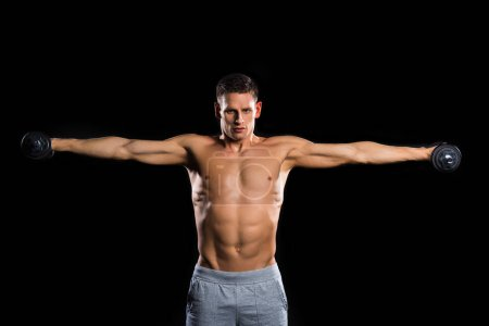 muscular shirtless sportsman holding dumbbells and looking at camera isolated on black