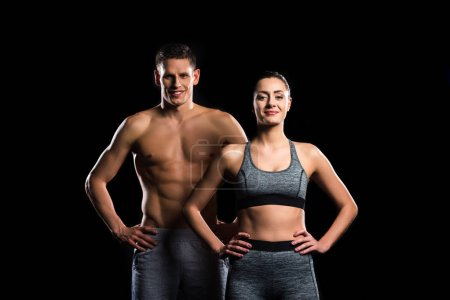 sporty young couple standing together and smiling at camera isolated on black