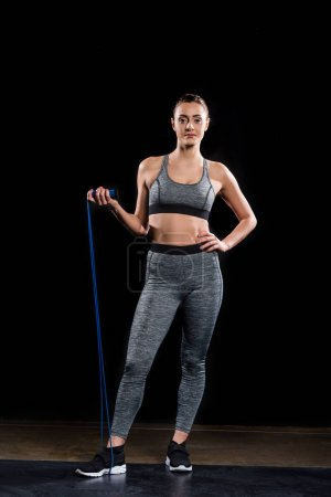 athletic young sportswoman holding skipping rope and looking at camera on black