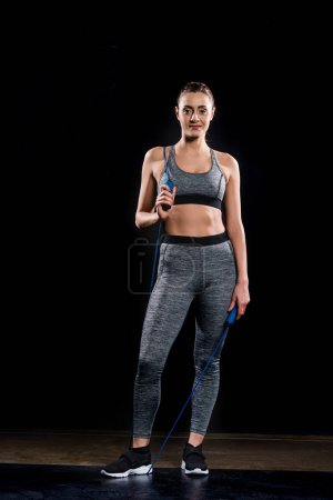 confident young sportswoman holding skipping rope and looking at camera on black