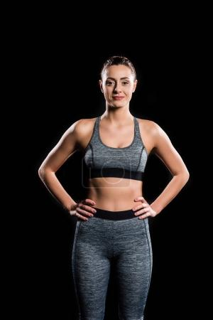 athletic young woman in sportswear looking at camera isolated on black