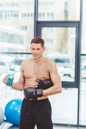 young muscular sportsman in boxing gloves drinking water from bottle and looking at camera in gym