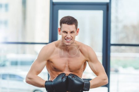 young shirtless muscular boxer in boxing gloves looking at camera in gym