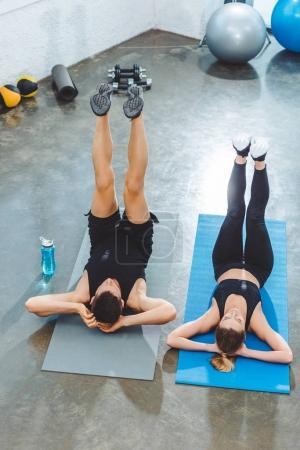 Photo pour Vue grand angle sportif jeune couple exerçant sur des tapis d'yoga dans une salle de sport - image libre de droit