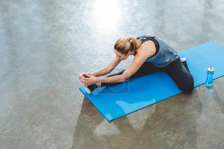 high angle view of young sportswoman exercising on yoga mat in fitness studio