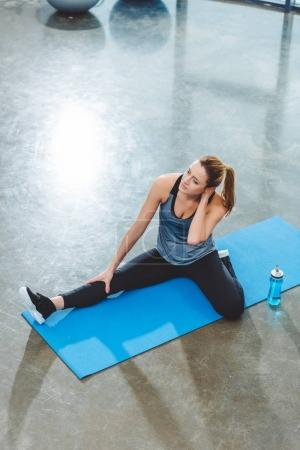 high angle view of young sportswoman sitting on yoga mat and exercising in gym